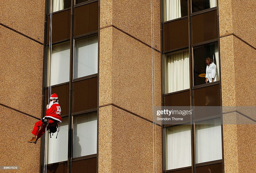 A women in a bathrobe watches from her hotel room as a Santa abseils down the front of Sydney's Four Season's Hotel to launch the Sydney Santa Fun Run on August 5, 2009 in Sydney, Australia. The children's charity Variety are hosting the event on November 29 for which they hope to encourage 5000 Sydney-siders to wear a Santa suit and raise funds for disadvantaged children.