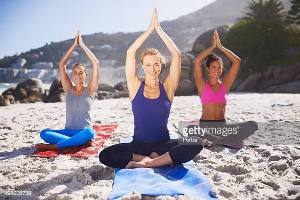 Women in an outside yoga class at beach