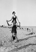 A women in bathing costume balancing on the shoulders of a man with another woman kneeling between his legs at a sandy beach Just behind them are...