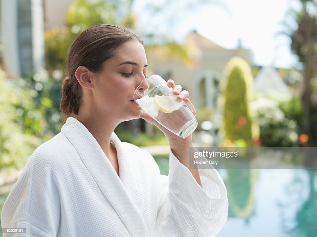 Women in bathrobe by a pool and drinking a water : Stock Photo