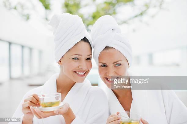 Femme en peignoir boire du thé au spa