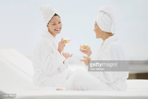 Women in bathrobes enjoying tea poolside at spa