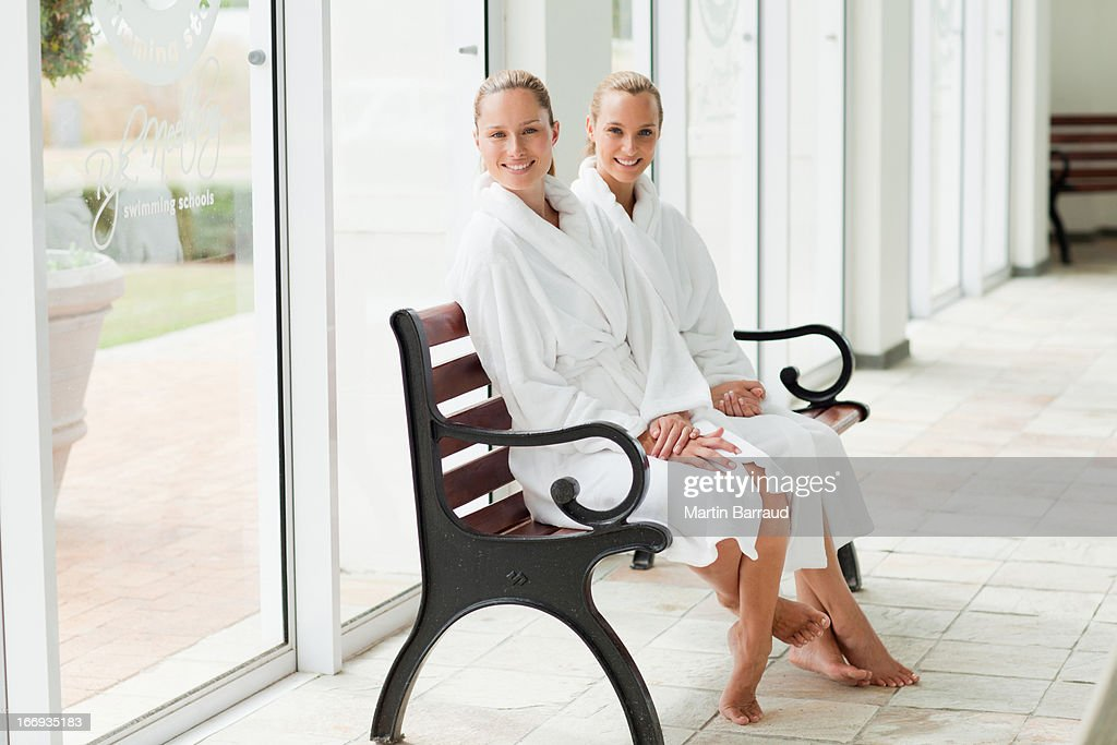 Women in bathrobes sitting on bench poolside at spa : Stock Photo
