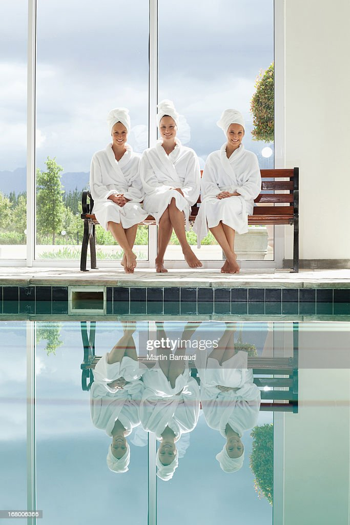 Women in bathrobes talking on bench poolside at spa : Stock Photo