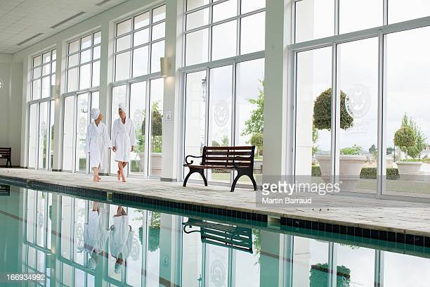 Femmes en peignoirs marchant le long de la piscine du spa