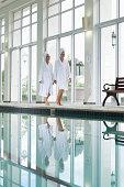 Women in bathrobes walking along swimming pool at spa