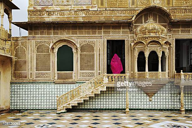 Women in beautifully decorated pink sari entering the Mandir Palace Heritage Hotel. Built in the traditional Haveli style, this hotel is over two centuries old. Jaisalmer, India. (MR)