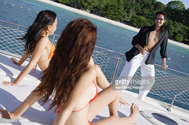 Women in bikinis sitting on boat deck, man standing, looking at them