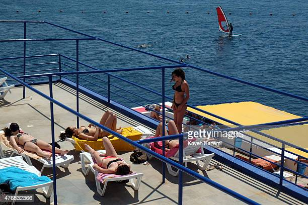 Women in bikinis sunbathe on the terrace of Sporting Club Beach on a weekend day on May 16 2015 in Beirut Lebanon Sporting Club is located on the sea...