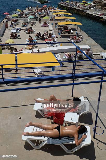 Women in bikinis sunbathe on the terrace of Sporting Club Beach on May 16 2015 in Beirut Lebanon Sporting Club is located on the sea front along the...