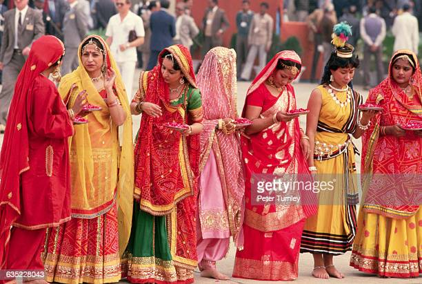 Women in brightly colored saris and bearing trays of flower petals wait to greet Mikhail Gorbachev in India on a state visit