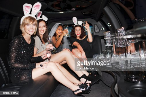 Women in bunny ears drinking champagne in limo : Stock Photo