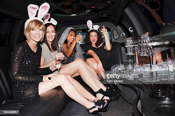 Women in bunny ears drinking champagne in limo