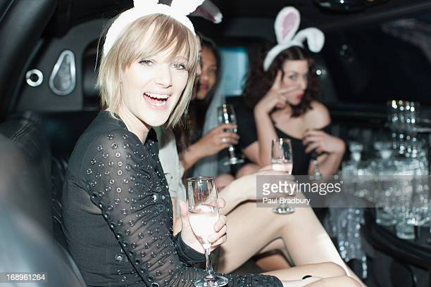 Women in bunny ears having champagne in back of limo