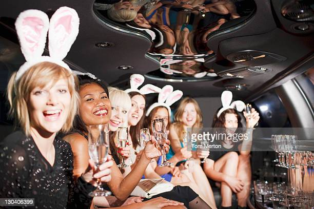 Women in bunny ears toasting in back of limo