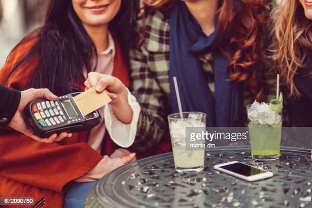 Women in cafe paying with credit card