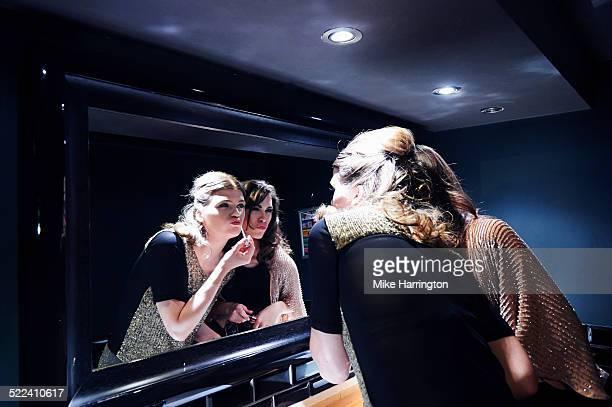 Women in club toilets applying lipgloss in mirror.