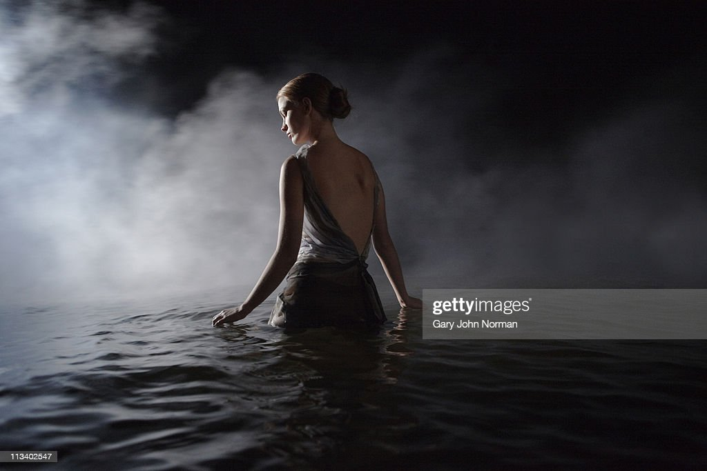 Women in dress appears through smoke : Stock Photo