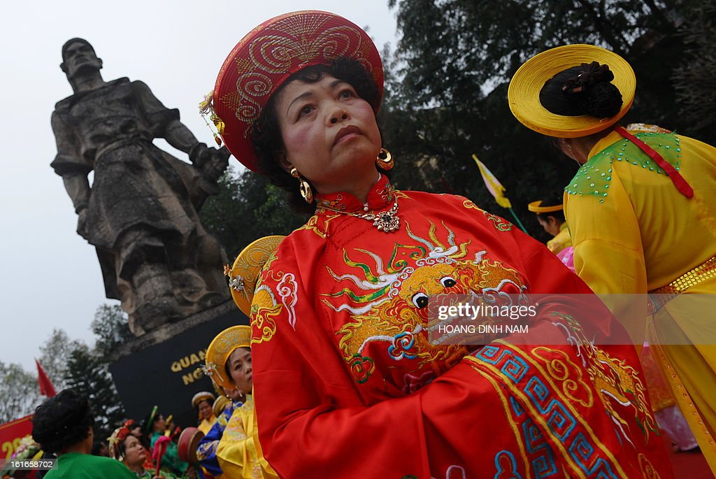 Women in festive dress perform a dance in front of the statue of King Quang Trung Trung during a ceremony to mark the 224th anniversary of Vietnam's Dong Da victory over Chinese invading troops in the spring of 1789 at the site of the historical battlefield in Hanoi on February 14, 2013. AFP PHOTO/HOANG DINH Nam
