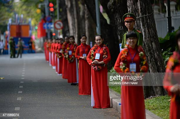 Women in festive red dresses stand along a street leading to the podium of a parade marking the 40th anniversary of the fall of Saigon in Ho Chi Minh...