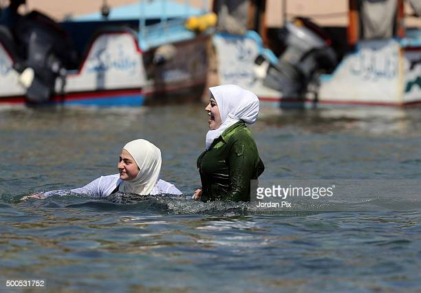 Women in headscarves bathe in the sea as tourists and Jordanians enjoy the sun and sea during the weekend on April 4 2015 in the southern city of...