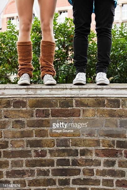 Femmes en jeans et jambières debout sur le mur