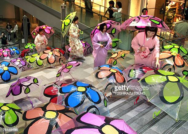 Women in kimono dresses walk through one hundred plastic umbrellas painted with colorful flowers for an art exhibition '100 umbrellas' by MireyHiroki...