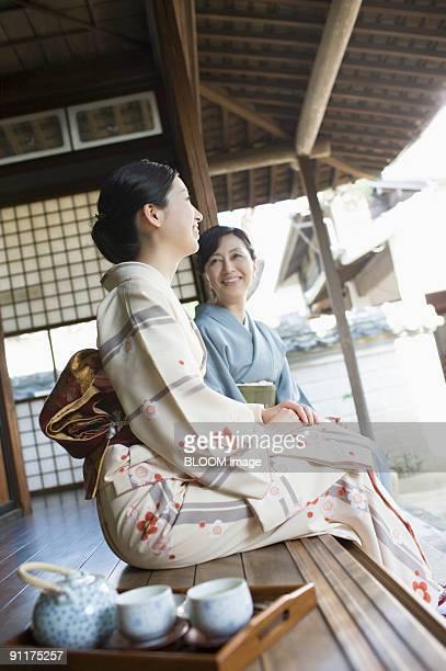 Women in kimono sitting on wooden deck