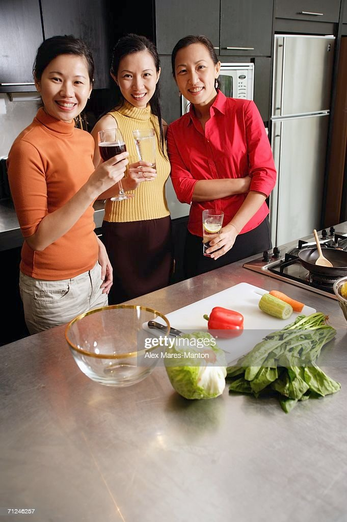 Women in kitchen, smiling at camera : Stock Photo