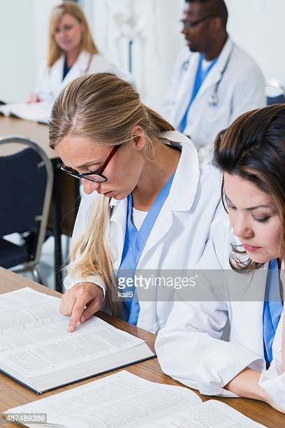 Women in lab coats training to be doctors