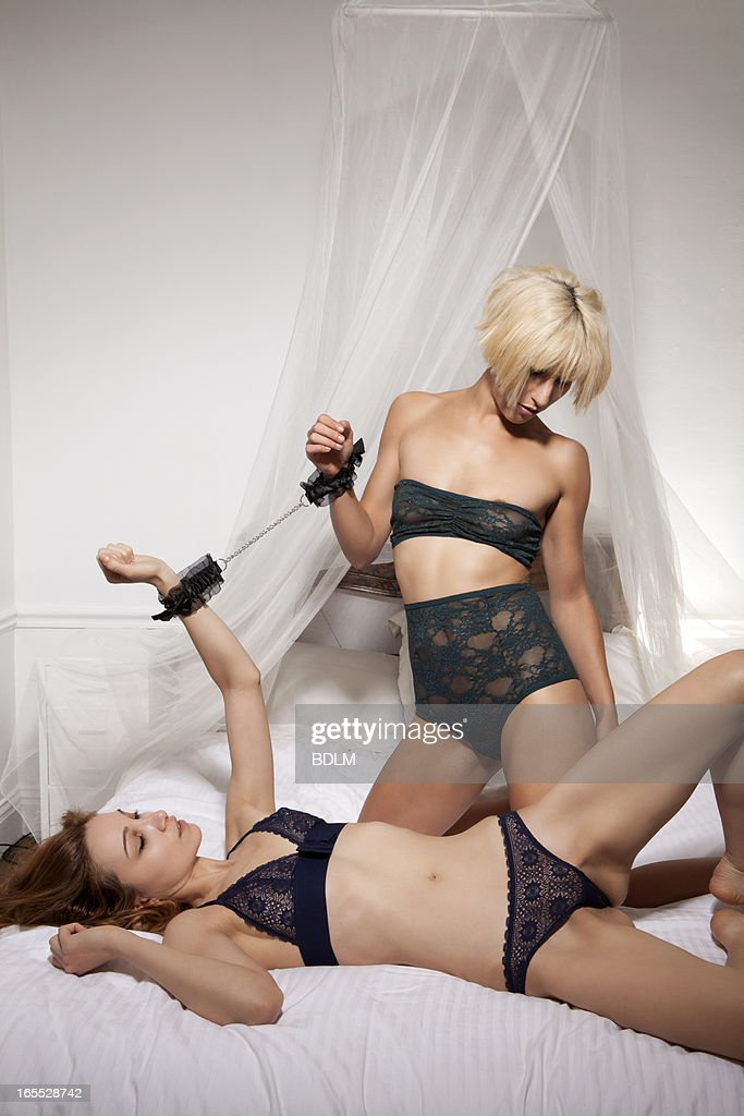 Women in lingerie in bed together : Stock Photo