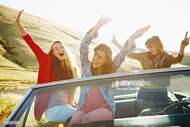 Women in parked convertible with arms in air