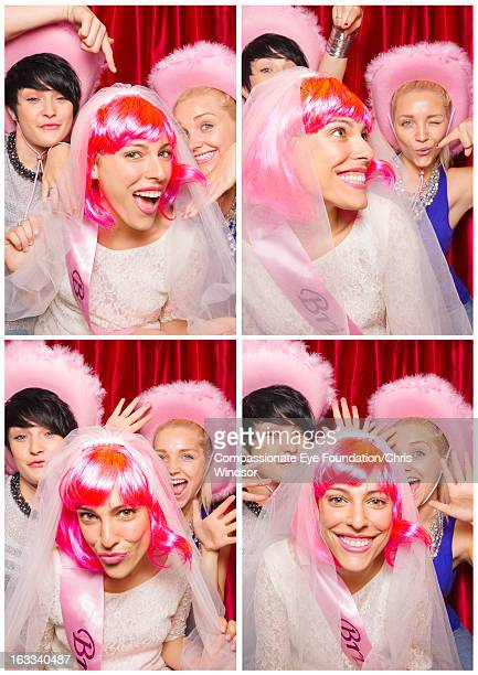 Women in photo booth, one wearing bridal veil