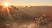 Women in purple dress sitting at edge of Grand Canyon
