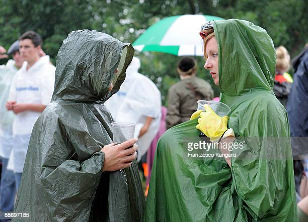 Women in rain ponchos chat over a drink during day two of the Glastonbury Music Festival at Glastonbury Festival site on June 26 2009 in Glastonbury...