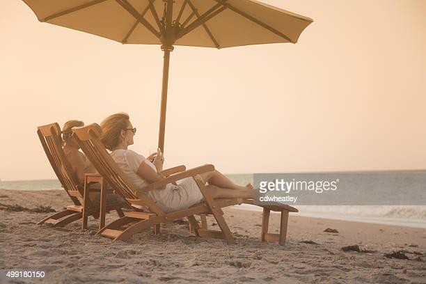 Donne a sdraio foderate sorseggiare un bicchiere di vino e tramonto