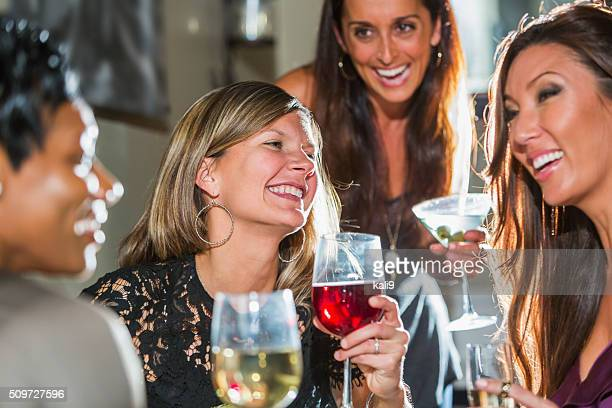 Women in restaurant with friends drinking and laughing