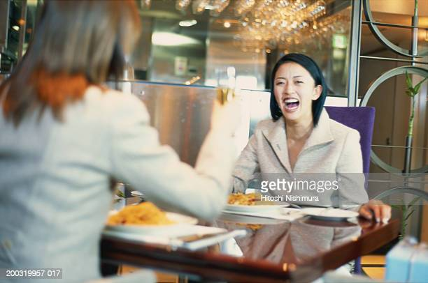 Women in restaurant with spaghetti and champagne, laughing