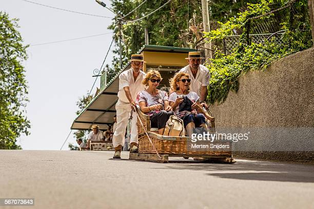 Women in sledge being pushed downhill