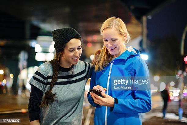 Women in sportswear using smart phone in city