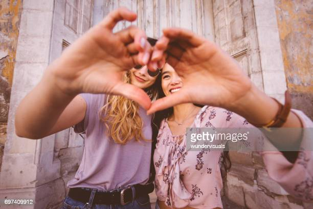 Women in the city making heart shape with their hands