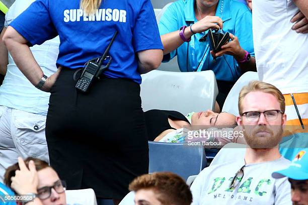A women in the crowd is attended to by paramedics during the first round match between Bernard Tomic of Australia and Denis Istomin of Uzbekistan...