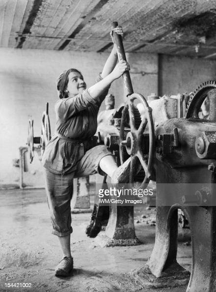 Women In The First World War Industry Transport and Agriculture A girl dressed in trousers and overalls brings both arms and a foot to bear as she...