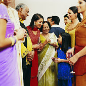 Women in Traditional Indian Dress Stand Talking to an Elderly Man at a Social Gathering