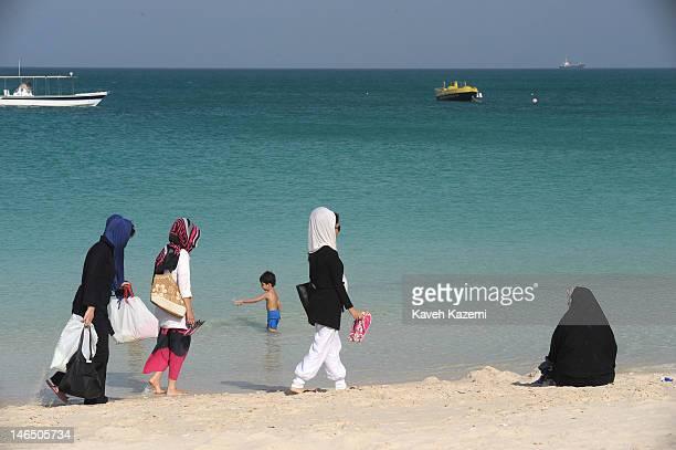Women in veils and short tunics walk past a woman in black chador sat on the sandy beach on April 13 2012 in Kish Iran Kish is a 915squarekilometre...