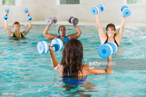 Women in water aerobics exercise class with instructor