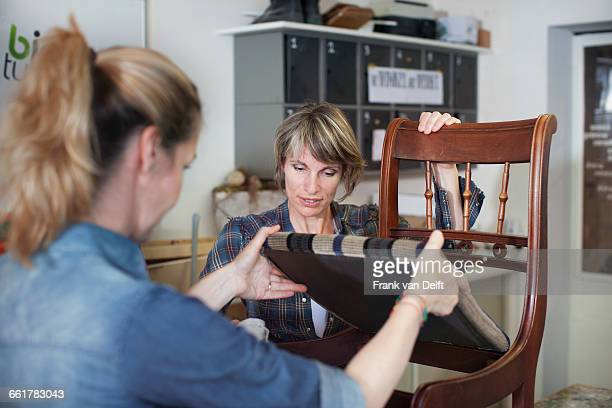 Women in workshop examining chair