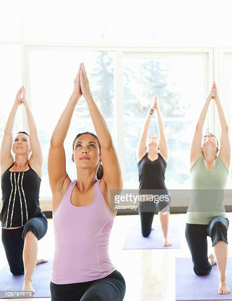 Women in yoga class practicing lunge pose