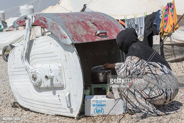 DEBAGA DIBAGA MAKHMOUR IRAQ Women is cooking in a trash container in Dibaga camp for Internally Displaced Person after the Iraqi Defense Forces...