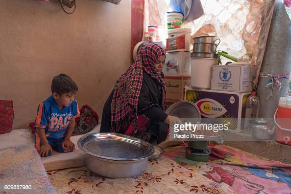 DEBAGA DIBAGA MAKHMOUR IRAQ Women is cooking in her tent in Dibaga for Internally Displaced Person after the Iraqi Defense Forces liberated their...